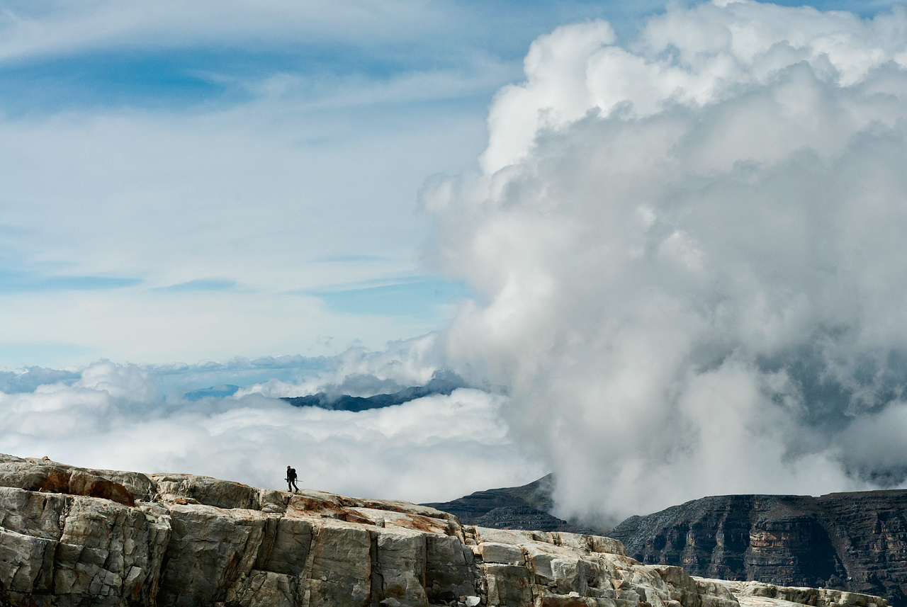 Towering clouds above a hiker in El Cocuy National Park, Colombia.