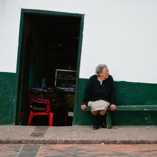 A woman sits outside of her business in Mongui, Colombia.